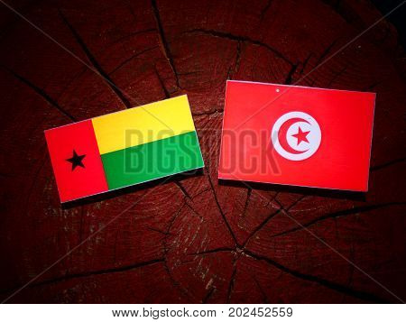 Guinea Bissau Flag With Tunisian Flag On A Tree Stump Isolated