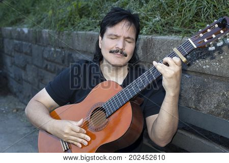 A hispanic man plays an acoustic nylon string guitar with passion outdoors.