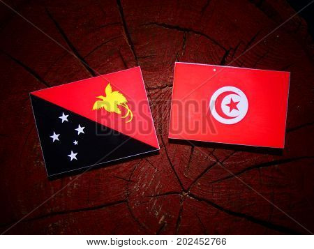 Papua New Guinea Flag With Tunisian Flag On A Tree Stump Isolated