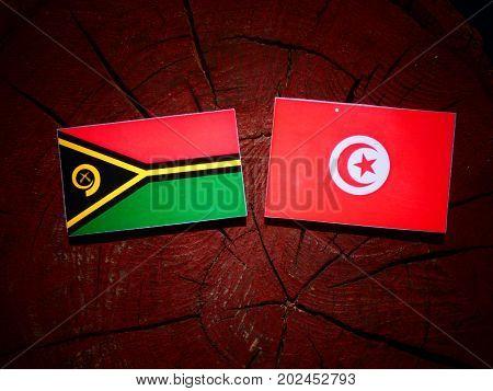 Vanuatu Flag With Tunisian Flag On A Tree Stump Isolated