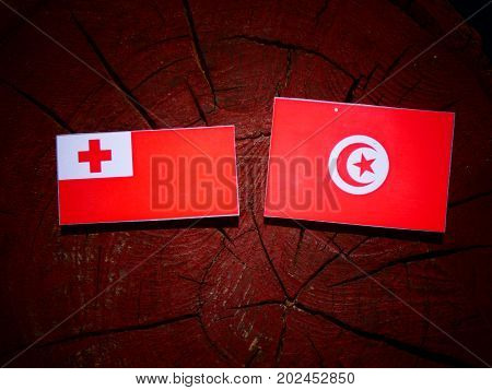 Tongan Flag With Tunisian Flag On A Tree Stump Isolated