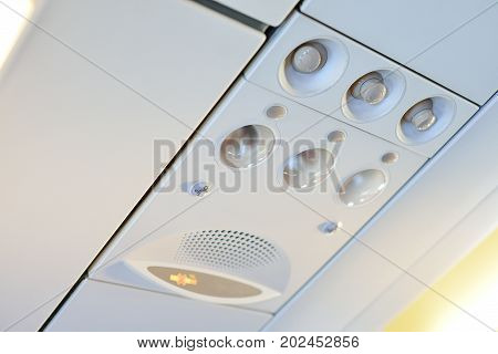 Overhead vents and lights in an airplane.