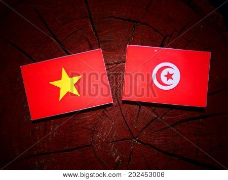 Vietnamese Flag With Tunisian Flag On A Tree Stump Isolated
