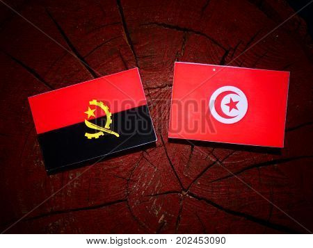 Angolan Flag With Tunisian Flag On A Tree Stump Isolated