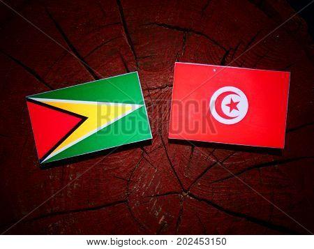 Guyana Flag With Tunisian Flag On A Tree Stump Isolated