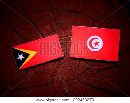 East Timorese Flag With Tunisian Flag On A Tree Stump Isolated