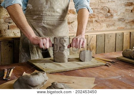 potter clay workshop ceramics art concept - male cuts raw clay with the string cutter closeup on hands of standing man dressed in an apron ceramist work over wooden table with sculpting tools set