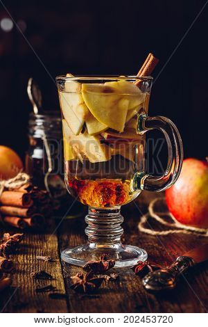 Glass of Apple Mulled Drink with Clove, Cinnamon, Anise Star and Dark Candy Sugar. All Ingredients and Some Kitchen utensils on Wooden Table. Vertical.