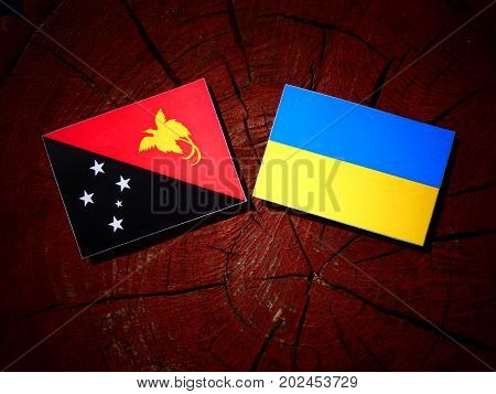 Papua New Guinea Flag With Ukrainian Flag On A Tree Stump Isolated