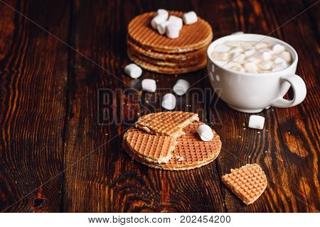 Stroop Waffles with Broken One with White Cup of Hot Chocolate with Marshmallow and Waffle Stack. Copy Space on the Left.