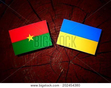 Burkina Faso Flag With Ukrainian Flag On A Tree Stump Isolated