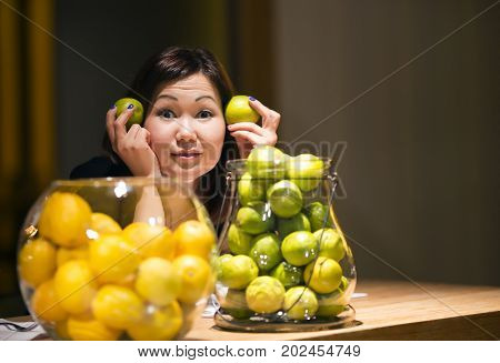 SPAIN, BARCELONA, MARCH,15, 2015 - Funny girl next to vases with lemons and limes at the celebration of the birthday of friends in the hotel W in Barcelona, Spain