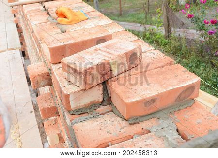 Bricklaying Brickwork. Bricklaying on House Construction Site. Installing Red Blocks and Caulking Brick Masonry Joints Exterior Wall.