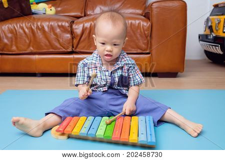 Portrait of Cute little Asian 18 months / 1 year old baby boy child hold sticks & plays a musical instrument colorful wooden toy xylophone Educational toy for kids and toddlers concept