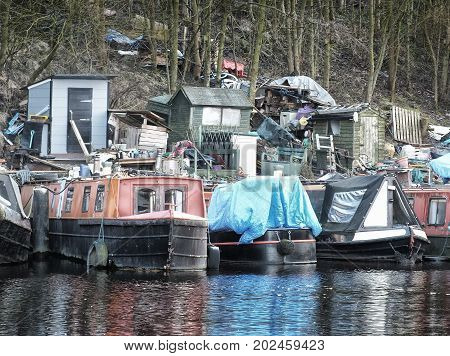 canal boats used for living in moored on a permanent site with sheds and clutter