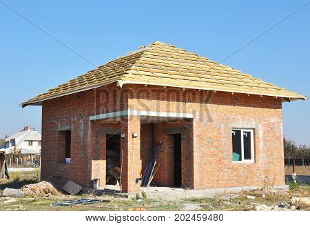 Roofing Construction Exterior with Red Brick House Wall Construction Facade.