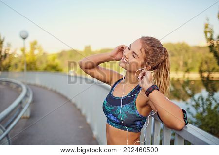 A happy girl jogger listens to music on headphones on a bridge in the summer city of the city.
