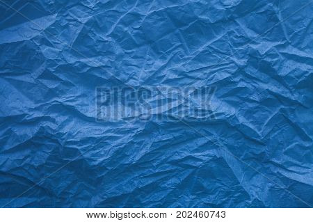 Rough blue paper texture. Blue crumpled paper texture and background. Close up view of wrinkled blue texture made with paper. Blue abstract texture and background for designers.