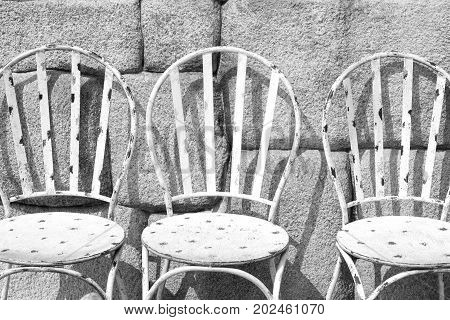 Image of white iron chairs on tropical garden