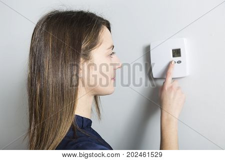 A woman set the thermostat at home