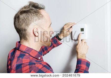 A men set the thermostat at home