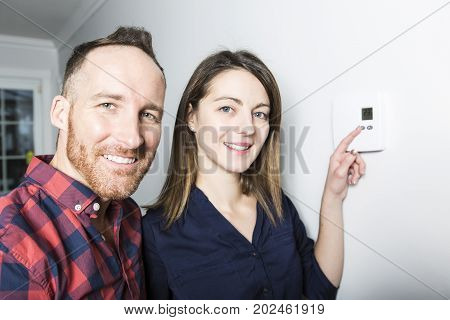 A couple set the thermostat at home