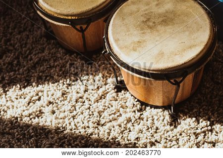 Musical instruments music passion and hobby obejcts concept. Detailed closeup of bongos on fluffy carpet
