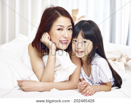 portrait of an asian mother and daughter lying on front in bed looking at camera smiling.