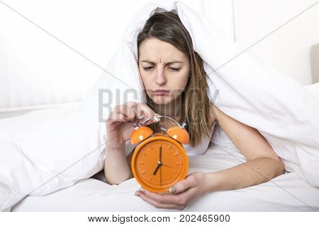 A Young sleeping woman and alarm clock in bedroom at home