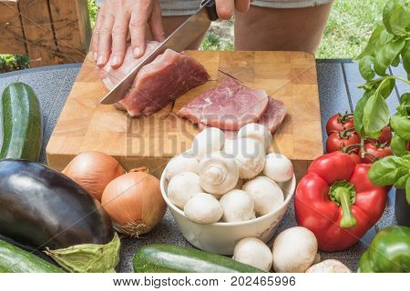 Front view of woman slicing meat on a wooden board. Various types of vegetables are lying on the table.