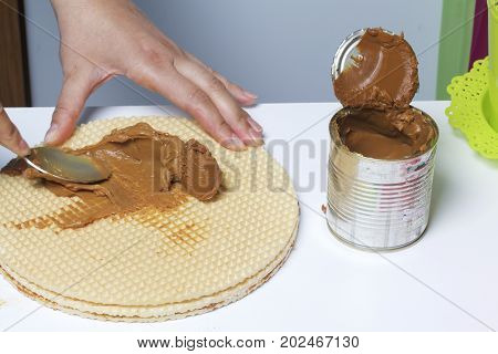A Woman Is Spreading Condensed Milk On A Waffle Cake. Waffle Cake With Boiled Condensed Milk And Cho