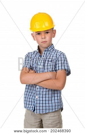 Serious cute boy in blue checkered shirt, grey jeans and yellow building helmet, isolated on white background.