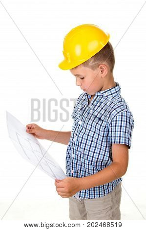 Clever little kid in yellow helmet and blue checkered shirt holding a building paper plan in hands, isolated on white background. Construction