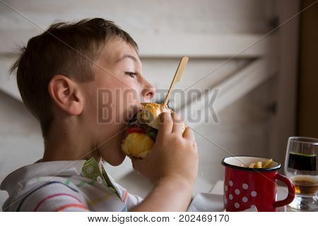Young boy eats big hamburger and chips