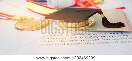 Concept of Success international education graduation black cap on roll up on letters diploma medals and passport for work and studying competition on abroad in famous institution.