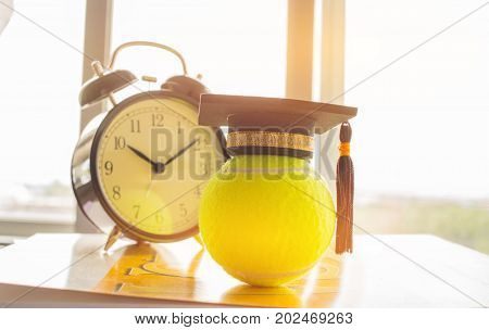 Graduation cap Put on Ball with clock Tennis is a racket sport can be played individually against single opponent Sports competition success concept