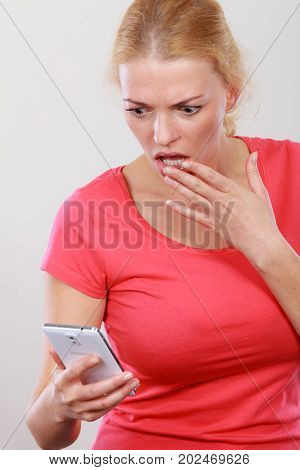 Human reaction and expressions technology modern devices concept. Shocked worried woman looking at phone she cant believie in bad news or message