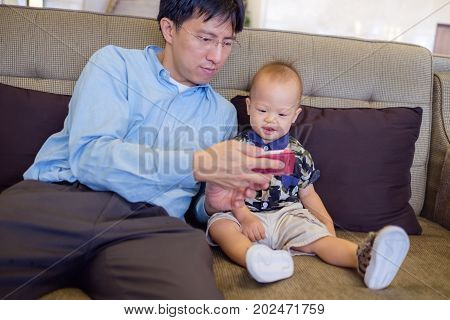Father and son are using smartphone while spending time together Dad and Cute smiling little Asian 1 year old toddler baby boy child sitting on sofa leisure & technology & internet addiction concept