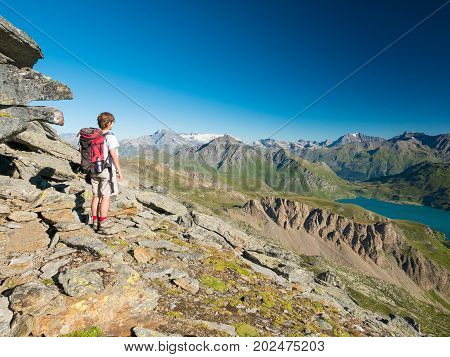 Woman Trekking In High Altitude Rocky Mountain Landscape. Summer Adventures On The Italian French Al