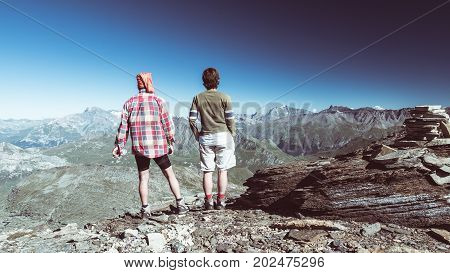 Couple of hiker on the mountain top looking at expasnive view and mountain peaks. Summer adventures on the Alps. Wide angle view from above toned image rear view.