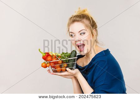 Buying good food vegetarian products. Positive woman holding shopping basket with green red vegetables inside recommending healthy high fibre diet lifestyle modification on grey