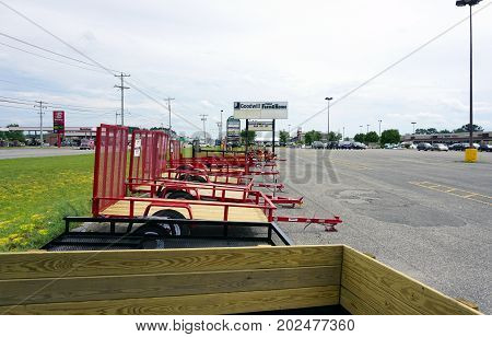 CADILLAC, MICHIGAN / UNITED STATES - JUNE 22, 2017: Trailers offered for sale, by Family Farm and Home, are displayed in a corner of the parking lot of the Village at Wexford Shopping Center on Mitchell Street.