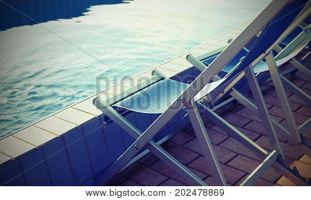 Empty Deck Chairs On The Pool Edge Of The Spa Without People