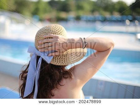 young woman with straw hat tans in the exclusive luxury resort on the edge of the pool