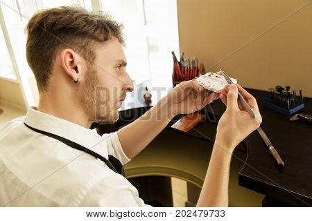 A Jeweler's Man Looks At A Stone To Create A Ring