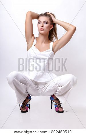 Girl In White Clothes Posing In The Studio On The Floor On A White Background