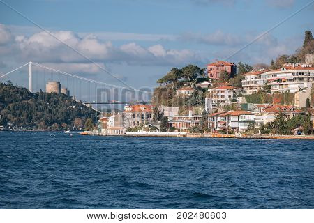 Rumelian Castle and Fatih Sultan Mehmet Bridge with background of Bosphorus strait cityscape on a sunny day with background cloudy blue sky and blue sea in Istanbul Turkey. Blue Turkey concept.