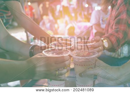 Friends clinking glasses above table.People holding glasses. cheering and celebration concept.