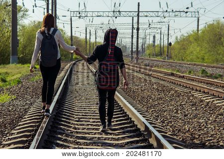 Back view of beautiful young couple walking far away on railroad together