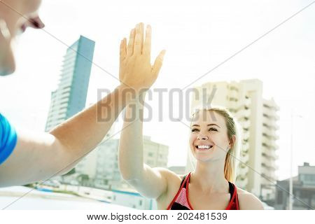 Two positive young friends high fiving each other after a workout while standing together outdoors on a sunny day